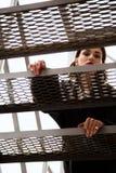 Forme o retrato exterior da mulher à moda na rua, nas escadas do metal com vista na cidade Fotografia de Stock Royalty Free