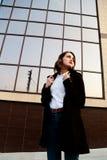 Forme o retrato exterior da mulher à moda na rua perto da construção do vidro Imagens de Stock