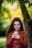 Forme o retrato exterior da mulher de sorriso lindo no casaco de cabedal marrom com o copo do coffe Menina elegante na roupa na m fotos de stock royalty free