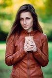 Forme o retrato exterior da mulher longa lindo do cabelo no casaco de cabedal marrom - estilo do outono Moça elegante no coágulo  imagem de stock royalty free