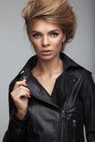 Forme o tiro da menina com penteado bonito em um casaco de cabedal fotografia de stock