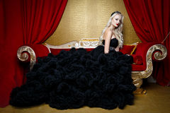 Forme o tiro da mulher loura bonita em um vestido preto longo que senta-se no sofá Imagens de Stock