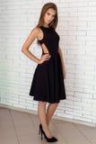 Forme o tiro de uma menina 'sexy' bonita em um vestido preto em um fundo de uma parede branca do tijolo no estúdio Foto de Stock