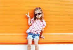 Forme os óculos de sol vestindo da criança à moda da menina e a camisa quadriculado que têm o divertimento na cidade Fotos de Stock Royalty Free