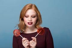 Forme os bordos de sopro da mulher do retrato com o pirulito de dois vermelhos imagens de stock