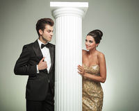 Forme os pares elegantes que olham se perto da coluna foto de stock royalty free