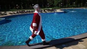 Forme Papá Noel que camina alrededor de piscina del ` s del hotel almacen de video