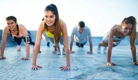 Forme physique, amiti?, sport et concept sain de mode de vie - groupe d'exercice heureux d'amis photographie stock