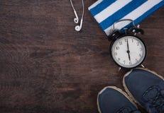 Forme physique avec l'horloge, les chaussures, la serviette et les écouteurs Images libres de droits