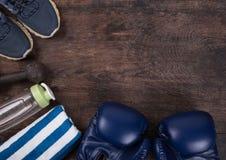 Forme physique avec une eau de bouteille, les chaussures, la serviette, les écouteurs et les gants de boxe Photos libres de droits