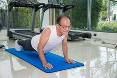 Forme physique d'homme supérieur s'exerçant en faisant des pousées au centre de fitness Image stock