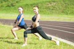 Forme physique et amies caucasiennes en bonne santé de LifestyleTwo ayant l'étirage de corps et les idées et les concepts de reco Image stock
