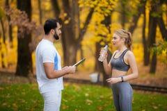 Forme physique Exercice personnel de femme de Takes Notes While d'entra?neur ext?rieur photographie stock libre de droits