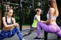 Forme physique extérieure Jeunes athlètes féminins s'étirant avant le fonctionnement en parc Photo libre de droits