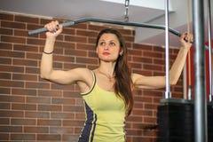 Forme physique La jeune belle fille blanche dans un costume jaune et gris de sports fait des exercices sur des appareillages de f photo libre de droits