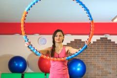 Forme physique La jeune belle fille blanche dans un costume rose de sports fait des exercices physiques avec un cercle au centre  Photos stock
