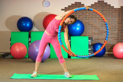 Forme physique La jeune belle fille blanche dans un costume rose de sports fait des exercices physiques avec un cercle au centre  Images libres de droits