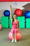 Forme physique La jeune belle fille blanche dans un costume rose de sports fait des exercices physiques avec une boule rose d'aju Images libres de droits
