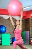 Forme physique La jeune belle fille blanche dans un costume rose de sports fait des exercices physiques avec une boule rose d'aju Photo libre de droits