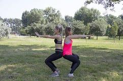 Forme physique Les filles travaillent s'accroupit ensemble maintenant l'équilibre lié au dos du corps images stock