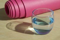 Forme physique rose roulée ou tapis et verre de yoga Photos stock