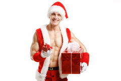 Forme physique sexy Santa Claus tenant des boîtes d'un rouge Image stock