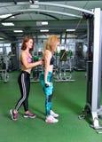 Forme physique, sport, exerçant le mode de vie - jeune femme et entraîneur personnel fléchissant des muscles dans le gymnase Photos stock