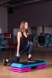 Forme physique, sport, formation, gymnase et concept de mode de vie - femme faisant un pas avec des haltères sur la plate-forme d Photos stock