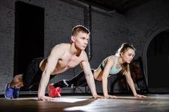Forme physique, sport, formation, gymnase et concept de mode de vie - jeune couple faisant des pousées dans le gymnase image stock
