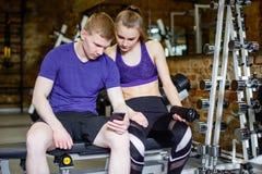 Forme physique, sport, technologie et concept de régime - femme et entraîneur personnel avec le smartphone et les bouteilles d'ea photo stock