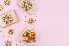 Forme presentes ou apresente caixas com curvas douradas e confetes da estrela na opinião de tampo da mesa cor-de-rosa Configuraçã imagem de stock royalty free