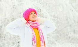 Forme a retrato do inverno a mulher feliz que veste um lenço feito malha colorido da camiseta do chapéu sobre o fundo nevado fotografia de stock