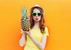 Forme a retrato la muchacha fresca en gafas de sol con la piña sobre naranja colorida Fotografía de archivo libre de regalías
