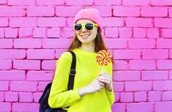 Forme a retrato la muchacha sonriente bonita con la piruleta sobre colorido Fotografía de archivo