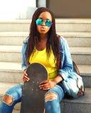 Forme a retrato la mujer africana joven con las gafas de sol del monopatín que se divierten Fotografía de archivo