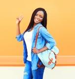 Forme a retrato la mujer africana joven sonriente feliz con la mochila sobre naranja Fotografía de archivo