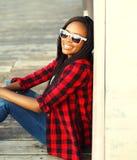 Forme a retrato la mujer africana sonriente feliz que lleva sentarse a cuadros rojo de la camisa y de las gafas de sol Foto de archivo