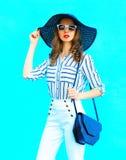 Forme a retrato la mujer joven que lleva un sombrero de paja, pantalones blancos y un embrague del bolso sobre el fondo azul colo foto de archivo