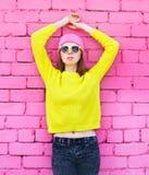 Forme a retrato la mujer joven que presenta sobre ladrillo rosado colorido Imagenes de archivo
