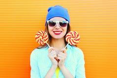 Forme a retrato la mujer joven sonriente feliz con una piruleta en el palillo sobre naranja colorida Imagen de archivo