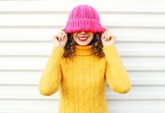 Forme a retrato la mujer sonriente joven feliz que lleva el sombrero hecho punto rosa colorido sobre blanco Fotos de archivo
