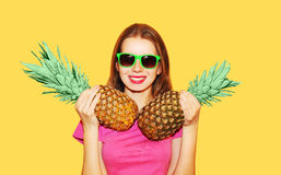 Forme a retrato la mujer y la piña sonrientes bonitas dos en gafas de sol sobre amarillo Foto de archivo