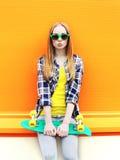 Forme a retrato llevar bonito de la muchacha las gafas de sol con el monopatín Imagen de archivo