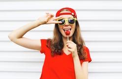 Forme a retrato a menina fresca com o pirulito que tem o divertimento sobre o branco Foto de Stock Royalty Free