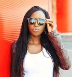 Forme a retrato a mulher africana nova em óculos de sol pretos na cidade sobre o vermelho imagens de stock