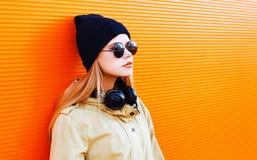 Forme a retrato a mulher loura com fones de ouvido, óculos de sol e chapéu negro em um fundo colorido alaranjado Imagens de Stock Royalty Free