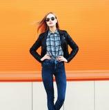 Forme a roca que lleva de la mujer bastante rubia el estilo negro sobre naranja Fotografía de archivo libre de regalías