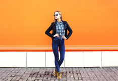 Forme a roca que lleva de la mujer bonita el estilo negro sobre naranja Fotografía de archivo libre de regalías