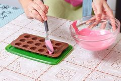 Forme rose fondue de chocolat et de coeurs Photographie stock libre de droits