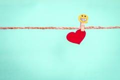 Forme rouge de coeur accrochant sur la corde avec l'agrafe heureuse de visage pour r doux Images libres de droits